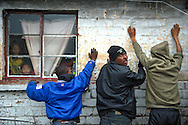 Suspected drug users with gang connections are stopped and searched by the Cape Town Metro Police Gang Unit on September 15, 2013 in Manenberg, a township of Cape Town, South Africa. The unit often works before sunrise in the community to execute search warrants and search for wanted criminals. Ann Hermes/© The Christian Science Monitor 2013