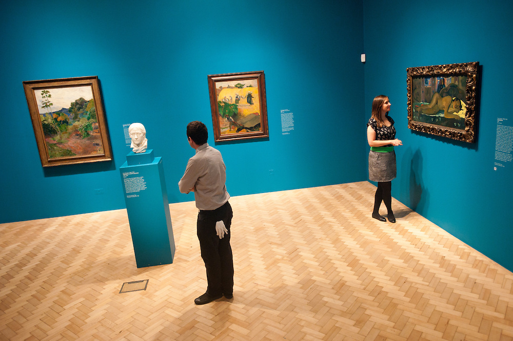London, UK - 19 June 2013: Hannah Talbot, marketing managar at the Courtauld Gallery and an art technician called Jack, stand next to paintings and a marble sculpture by Paul Gauguin at the Courtauld Gallery. The Courtauld Gallery opens tomorrow a special summer display of the most important collection of works in the United Kingdom by the Post-Impressionist master Paul Gauguin (1848-1903), assembled by the pioneering collector Samuel Courtauld (1876-1947).