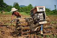 A farmer is plowing the fields with crude machinery in Nakhon Nayok, Thailand