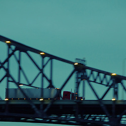 Late in the evening, a semi truck speeds across the tall and massive structure on the Chicago Skyway spanning the Calumet River.