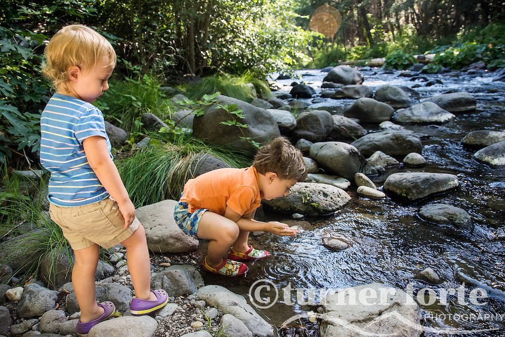 Toddler siblings looking for creatures in Deer Creek, California.