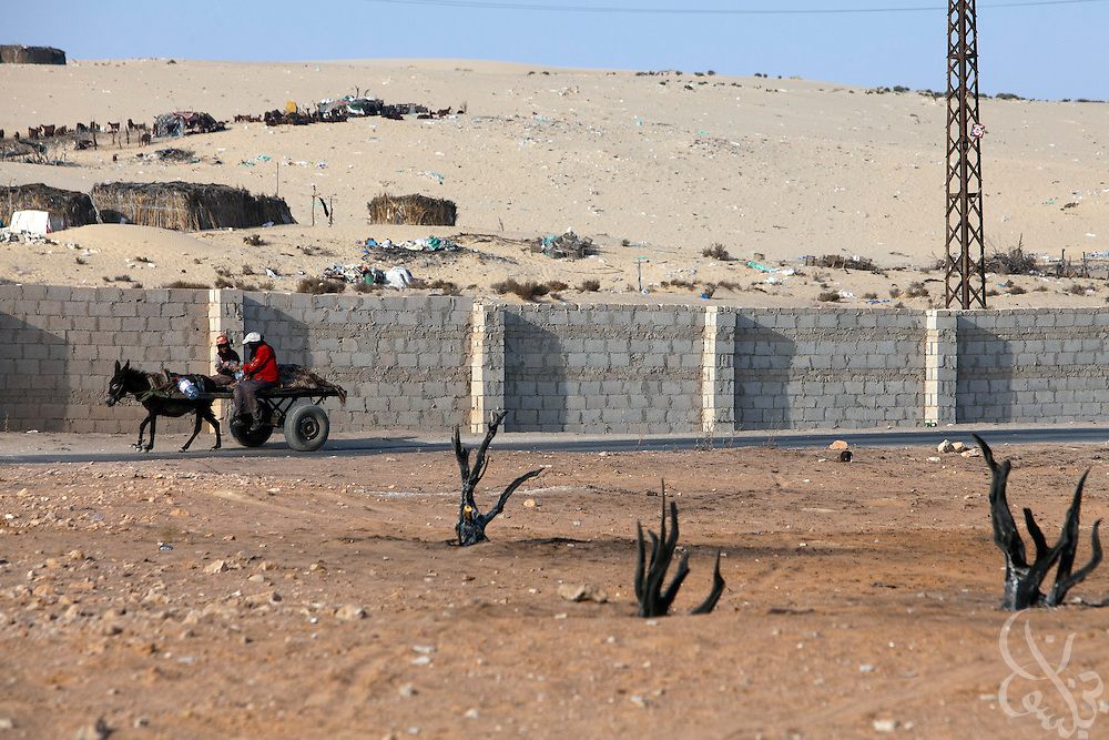 Bedouin women on a donkey cart ride past burnt tree stumps July 26, 2011 near a recently bombed natural gas pumping station, one of more than a dozen located just outside the North Sinai town of Areesh, Egypt (40 kilometers from the border with Israel.) Since the Egyptian revolution, a decline in the number of police across the Sinai has resulted in a boom in the smuggling business and a spate of bombings targeting the natural gas export pipeline to neighboring Israel..Slug: Sinai.Credit: Scott Nelson for the new York Times