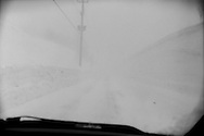 White out on mountain road in an Aomori blizzard that would soon make passage impossible with snow drifting across the road.  Near Harukaizawa village in the mountains of Aomori Prefecture.   Japan