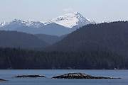 A man walks to his boat, moored at a tiny island along Canada's Inside Passage, surrounded by forested hills and snowy mountains