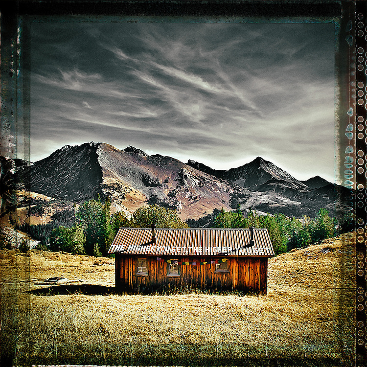 """Pioneer Cabin near Sun Valley Idaho with the Pioneer Mountain Range in the back ground. Taken at mid-day in the late fall,  Sign on roof reads: """"The higher you get, the higher you get""""  This cabin was built by the Sun Valley Company as a back country ski hut in the 1930's."""
