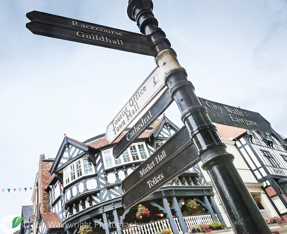 A signpost showing the range of attractions in Chester city centre.  In the background diners enjoy a view of the city from high up in the unique Rows.