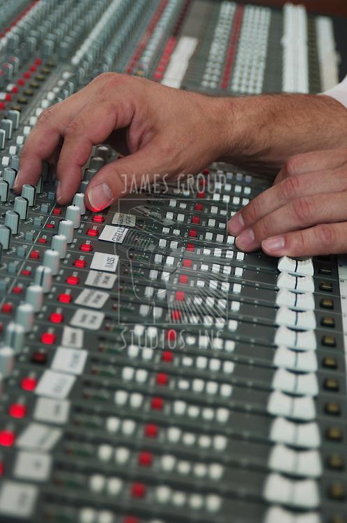 ssound technician's hand on audio mixer