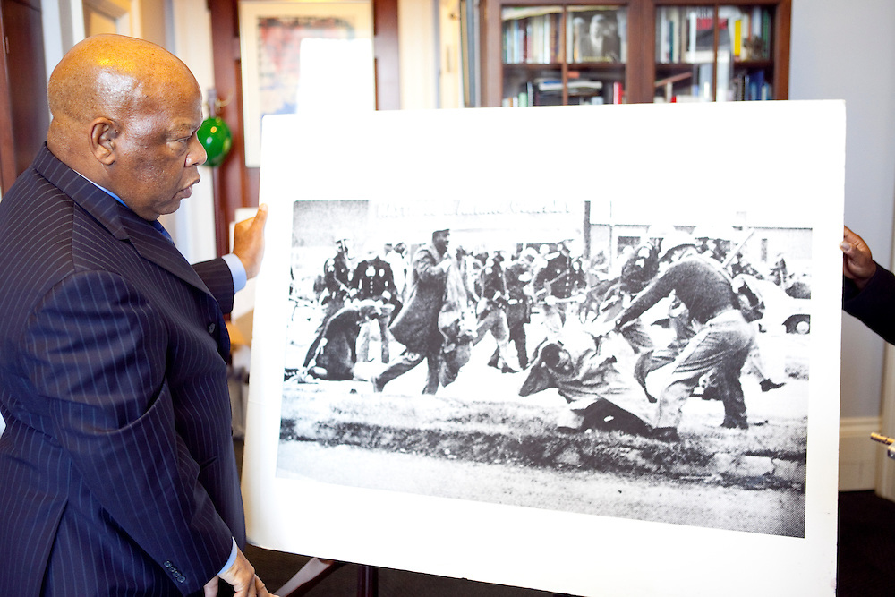Rep. John Lewis (D-GA) shows off a photo of him being beaten and arrested during the civil rights era after an interview in his office on Capitol Hill on Tuesday, Apr. 21, 2009 in Washington, DC.