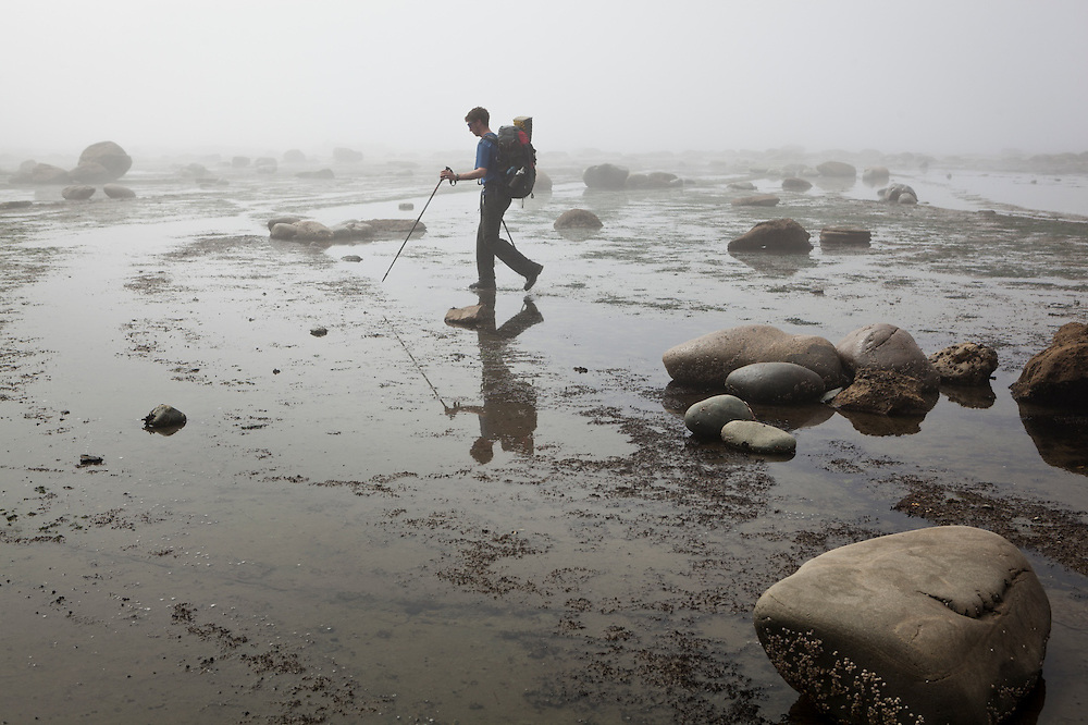 Zach Podell-Eberhardt hikes through shallow water on the continental shelf in the mist near Bonilla Point, West Coast Trail, British Columbia, Canada.