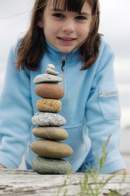 A young girl behind her stack of rocks balanced on a log.