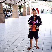 """Akha child wearing a Santa Claus hat at the premises of the NGO """"Children of the Golden Triangle"""", in Chiang Rai province"""