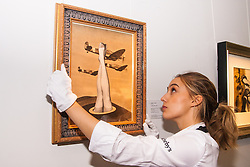 Sotheby's, Mayfair, London, November 7th 2014. Several outstanding examples of Czech avant-garde art from the Roy and Mary Cullen collection are to be auctioned by Sotheby's on November 12th. PICTURED: A Sotheby's worker hangs a collage by Teige which is expected to fetch £50,000 to £70,000 at auction.