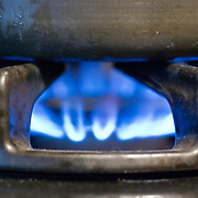 A cooking pot heats over a gas burner on a kitchen stove.