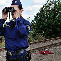 Hungarian policewoman by the Hungarian border using binoculars to look at refugees and migrants on the Serbian side. The old railway line, which runs through a gap in the border fence is a principal point of access for refugees and migrants heading for Western Europe.