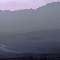 Well after sunset, the fog rolls in over the California coast as a lone car makes its way south on Highway 1 along the Pacific.