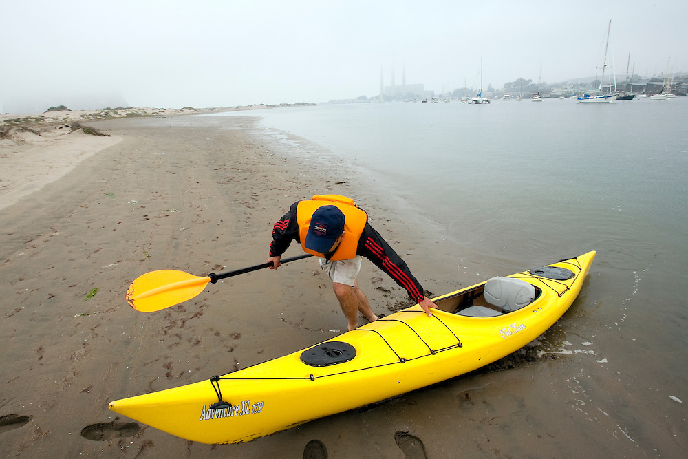 Pulling a kayak onto a small island in Morro Bay, California on a foggy, summer morning.