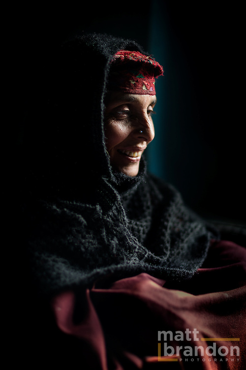 A Gujjar woman sits in her hut wearing her traditional hat that is unique to her the Pahari Gujjar women.