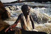 A young girl takes advantage of the low water level, at the height of the dry season, to fish in the small rapids of Wagenia Falls, near Kisangani, DR Congo.