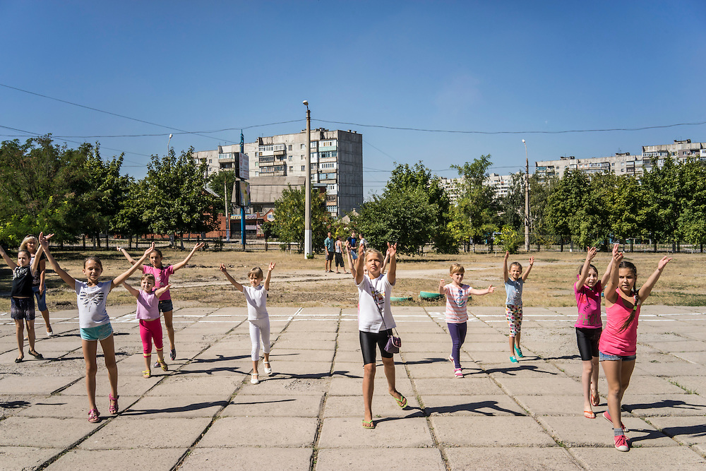 MARIUPOL, UKRAINE - AUGUST 31, 2015: Girls rehearse a dance production which they will perform on the first day of school at School 68 in Mariupol, Ukraine. A recent decrease in fighting has been credited to a desire to not interfere with the start of a new school year, planned for September 1. CREDIT: Brendan Hoffman for The New York Times