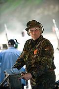 Die Maschinengewehr und Waffen Show in Knob Creek, Luisville, Kentucky, USA, ist die groesste seiner Art in Nordamerika. An drei Schiessstaenden werden Waffen aller Art abgefeuert, vor allem Schnellfeuergewehre. Auch Kinder duerfen hier das Schiessen mit dem Maschinengewehr ueben. Im Angebot ist auch ein Jungle Walk, auf welchem je ein Teilnehmer mit einer Uzi auf im Wald versteckte Metallscheiben schiesst..Bild: Ein Offizieller mit deutscher Flagge an der Uniform.Auf der grossen Schiessanlage werden alte Motorboote, Autos, Kuehlschranke, Computer etc  in Brand geschossen. Fuer die zahlreichen Regierungsgegner werden auch immer wieder gerne ausrangierte Wahlkabinen aufgestellt und mit Begeisterung zerschossen. ...