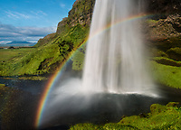 Wide angle shot featuring a dramatic rainbow at the base of Seljalandsfoss waterfall in southern Iceland