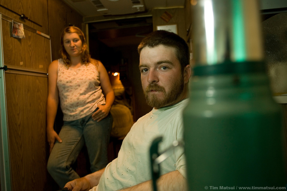 PINEDALE, WY - Welder Reed Helderman and his wife and helper Emily, of Oklahoma, relax in their trailer at the trailer park where they are living for several months in Pinedale, Wy., on August 10, 2005. The Helderman's, who own a home in Oklahoma, pay $420 per-month to stay at the trailer park. Rental housing and hotel rooms are hard to find in Pinedale because the town of 1400 is suffering from the pressures of a natural gas boom with gas field workers and private contractors occupying many of the rooms available. New high density construction proposals are often met with public resistance in spite of a cry for denser, more affordable housing. Farms and ranches are being broken up and sold typically as two, five, 10, and 20 acre lots on septic systems and well water which will make it difficult to extend town utilities past a growing ring of private lots. One of the local sayings is that the escalating real estate prices are a result of the billionaires moving into nearby Jackson, WY, who are pushing out the millionaires who then move to Pinedale. According to realtor Travis Bing, anything one 'would want to buy' starts at about $200,000 with many homes selling for $450,000 and up. Realtor Cyd Goodrich believes there is a shortage of low to middle income homes. Pinedale currently has the lowest unemployment rate in the state and is experiencing another boom cycle both in real estate and in energy as natural gas production in two nearby gas fields ramps up for year-round production.