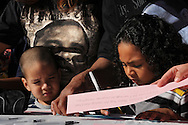 Damien Hackworth, 3, (left), watches Cameron Hackworth, 5, write a message for a large paper chain of messages written to the victims of the assassination attempt on Gabrielle Giffords.  They planned to attend the visit by President Obama to the University of Arizona.