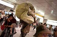 A man exits a train line carrying a huge fibre glass skull, in Shibuya, in Tokyo, Japan, on Saturday 26th September 2009.