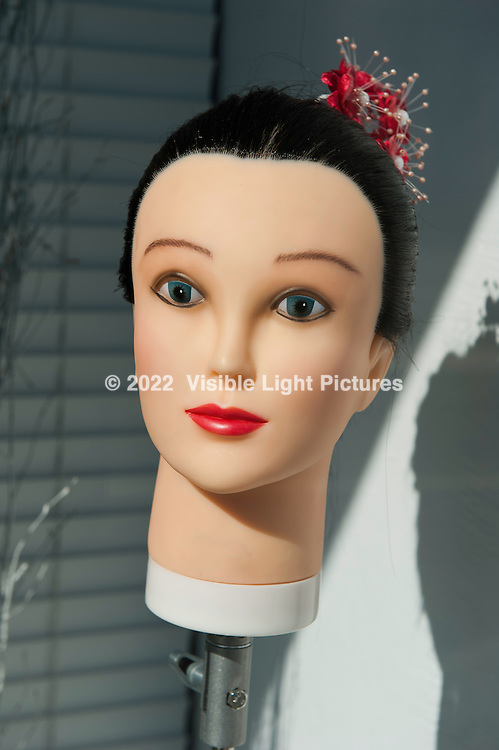 Beauty parlor mannequin in a storefront window.