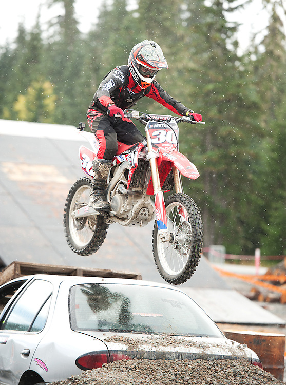 Endure Rider Remy Retailler jumps over a wrecked car during the All Terrain Moto Expo at the Whistler Olympic Park.  The event was raising money for the Canadian Spinal Cord Research Organization.  Saturday, Sept 3, 2016.  <br /> <br /> Photo:  David Buzzard