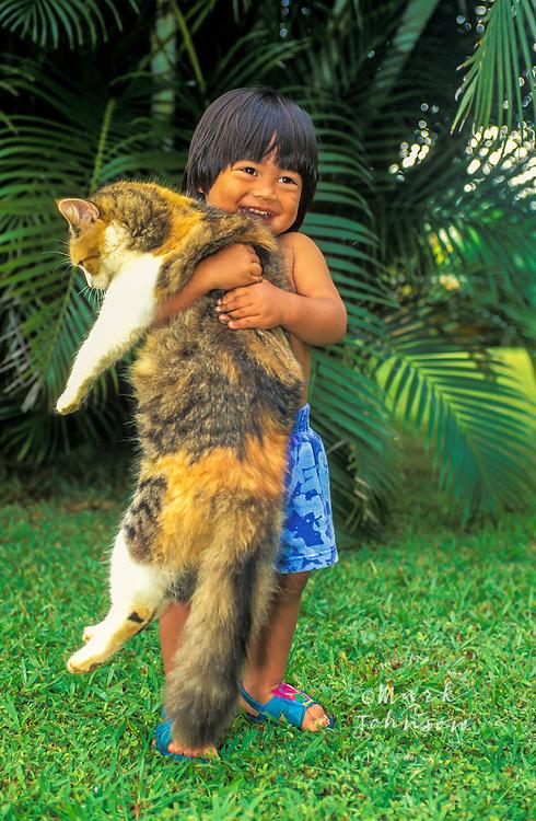 Happy 2 y.o. Hawaiian boy holding a large cat, Kauai, Hawaii