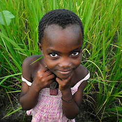 A Tanzanian childwalks home near sunset in the village of Usuru. The dense forest and tall grasses make villagers vulnerable to lion attacks. They have to stay late in the evening in their fields to protect their crops from rampaging monkeys who like to eat the rice and corn, forcing them to walk at sunset, the time of day when lions are out looking for prey.  Ami Vitale