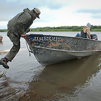 Peter Spein launches his skiff onto the Kwethluk River near the Yup'ik Eskimo village of Kwethluk, Alaska, where transportation is by boat, four-wheeler, and snowmachine. In winter the river becomes both ice road and landing strip.