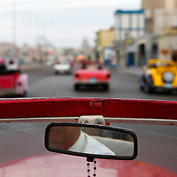 Central America, Cuba, Havana. Classic convertible driving on the Malecon in Havana.