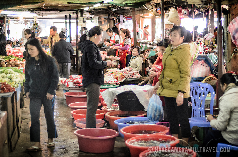 Vendors sell shellfish and fish from plastic tubs at the large and bustling morning market in Phonsavan in northeastern Laos. The people of the region are predominantly of Hmong ethnicity.