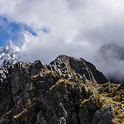 Day 3 of 10: From Alto de Pucaraju pass (15,300 ft or 4640 m), see Nevado Taulliraju (19,100 ft or 5830 m) rising behind the clouds. Trek 10 days around Alpamayo, in Huascaran National Park (UNESCO World Heritage Site), Cordillera Blanca, Andes Mountains, Peru, South America.