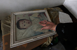 A Chinese villager of Xiangnan Village wipes dust from a picture frame of his grandson who has been sent away from the village to escape the pollution from nearby chemical plants in Zekou Town, Qianjiang City of Hubei Province, China 15 January 2013. While the heavy smog in Beijing and much of northern China in recent days have caused alarm among residents and renewed scrutiny on the pollution woes of the country, villagers in a small town of Hubei Province have been grappling with severe air, water and noise pollution on a daily basis over the past two years. China's Xinhua news reported 04 January 2013 that more than 60 cancer deaths in various villages of Zekou Town has been caused by the heavy pollution from the chemical industry park nearby. About 20 or more chemical plants built around the villages of Dongtan, Xiangnan, Zhoutan, Sunguai, Qingnian and others over the past two years has created huge increases in noise, air and water pollution. Many villagers complained of intensifying respiratory, heart, skin and circulatory illnesses caused by the pollution and a large spike in cancer diagnoses and deaths since the factories were built. .