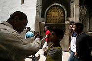 Man talking to a boy near Moulay Idriss Tomb. Moulay Idriss is the founder of Morocco and of Fes. His Zaouia (tomb) is considered the holiest building in the holy city of Fes. Although non-muslins can't get in, it's permitted to walk around.and see the  lovely brass dividers. Quiet and serene this place is beautiful and peaceful.