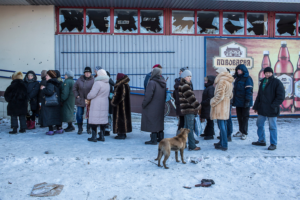 DEBALTSEVE, UKRAINE - FEBRUARY 20: Local residents gather to receive humanitarian aid outside a damaged supermarket on the central square on February 20, 2015 in Debaltseve, Ukraine. Ukrainian forces withdrew from the strategic and hard-fought town after being effectively surrounded by pro-Russian rebels, though fighting has caused widespread destruction. (Photo by Brendan Hoffman/Getty Images) *** Local Caption ***