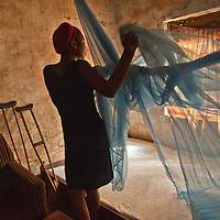 A nurse in rural Nigeria prepares a bednet.  Treated with insecticide, the nets can guard against the spread of mosquito-borne malaria.
