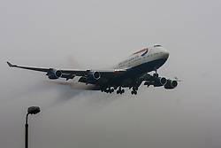 "January 3rd 2015, Heathrow Airport, London. Low cloud and rain provide ideal conditions to observe wake vortexes and ""fluffing"" as moisture condenses over the wings of landing aircraft. With the runway visible only at the last minute, several planes had to perform a ""go-round"", abandoning their first attempts to land. PICTURED: Water vapour streaming from its wings, a British Airways Boeing 747 Jumbo Jet emerges from the low cloud moments before touchdown on Heathrow's runway 27L."