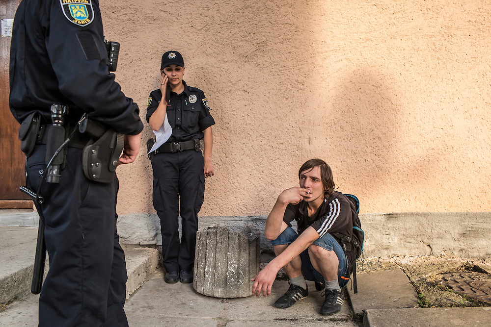 LVIV, UKRAINE - SEPTEMBER 16, 2015: Members of the new Lviv police including Tetiana Soroka, 25, center, take Vladimir, 26, right, outside for a cigarette after arresting him when he was found intoxicated and sleeping in the city's central square and then swore at police officers in Lviv, Ukraine. In an effort to reform the notoriously corrupt Ukrainian police force, an entirely new force has been established in several cities, including Kiev and Lviv, with a primary focus on patrolling the streets. CREDIT: Brendan Hoffman for The New York Times