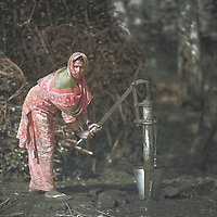 A veiled woman pumps water from a well located a few hundred metres from her village. As the constant flow of villagers is guaranteed, wells provide excellent photographic opportunities in rural India