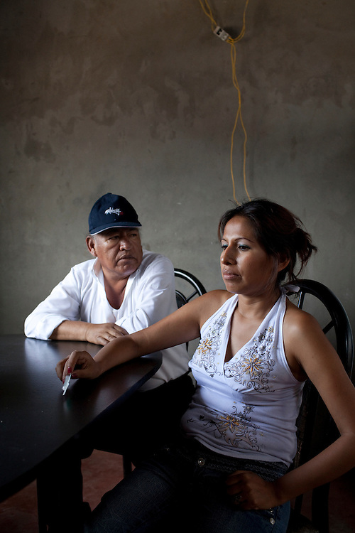 A woman sits with her father, who has tuberculosis, in their home on Monday, Apr. 13, 2009 in Ventanilla, Peru.