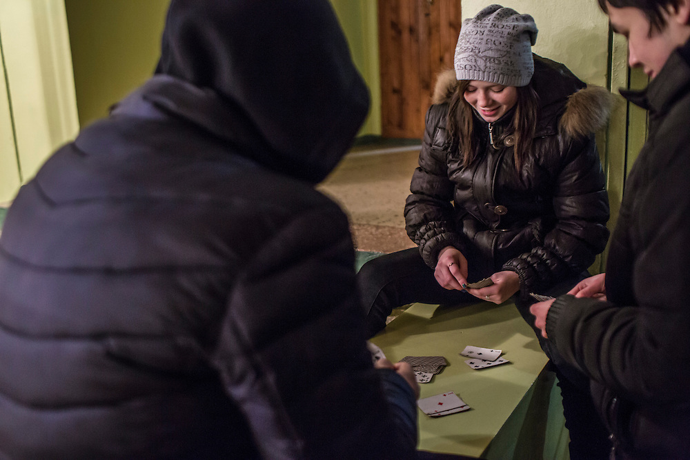 Teenagers play cards in the lobby of the local coal mine office building on Saturday, December 12, 2015 in Zolote, Ukraine. With no place else to hang out, young residents congregate at the mine.