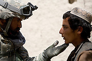 Battalion Cultural Advisor Zaki Khan, left of the 82nd Airborne's 1/508 PIR questions an Afghan youth in Sangin, Helman province, Afghanistan on Tuesday, April 10, 2007.