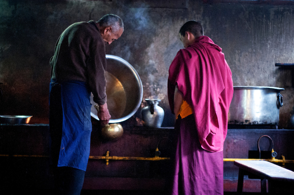 Lunchtime in a Monastery kitchen; a monk pours soup, while the other one patiently waits.