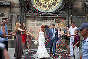 A young couple from Russia getting their wedding photograph done under the Prague astronomical clock, or Prague orloj which is a medieval astronomical clock located at Old Town Square in the capital of Czech Republic.