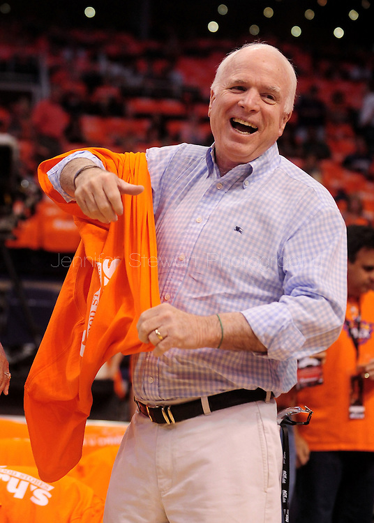 May 29, 2010; Phoenix, AZ, USA; US Senator John McCain puts on his orange Phoenix Suns tshirt prior to the first quarter in game six of the western conference finals in the 2010 NBA Playoffs at US Airways Center.  Mandatory Credit: Jennifer Stewart-US PRESSWIRE