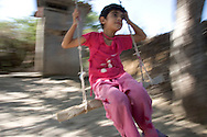 A girl plays on a swing at the Chalabixan camp for internally displaced people, located near Sheki, Azerbaijan.